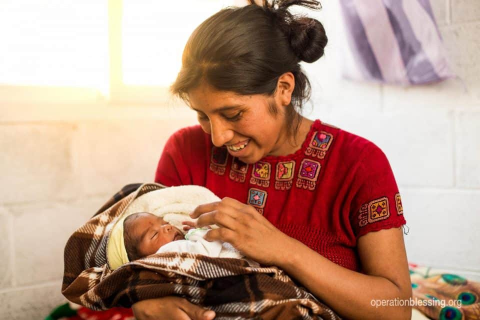 Fabiana holds her new baby in her new home after the earthquake.