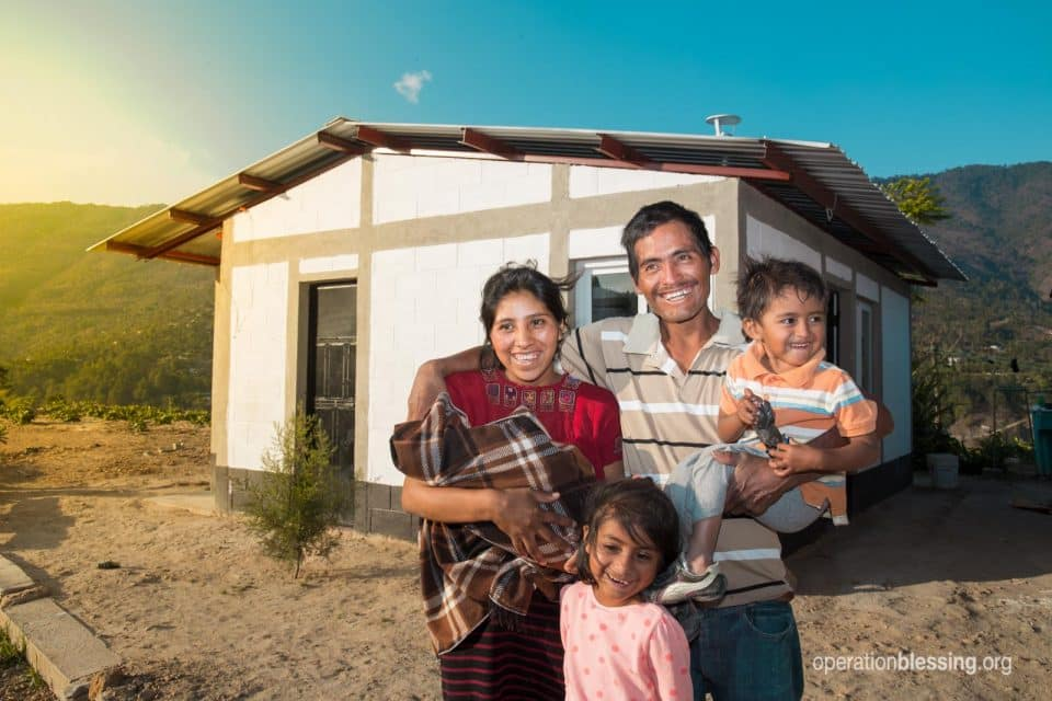 Arturo and family in front of the new home they received from Operation Blessing after an earthquake.