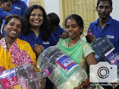 Cyclone Fani relief for victims in India who smile as they receive safe water.