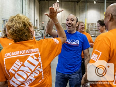 Operation Blessing worker high fives The Home Depot for Team Depot Day.