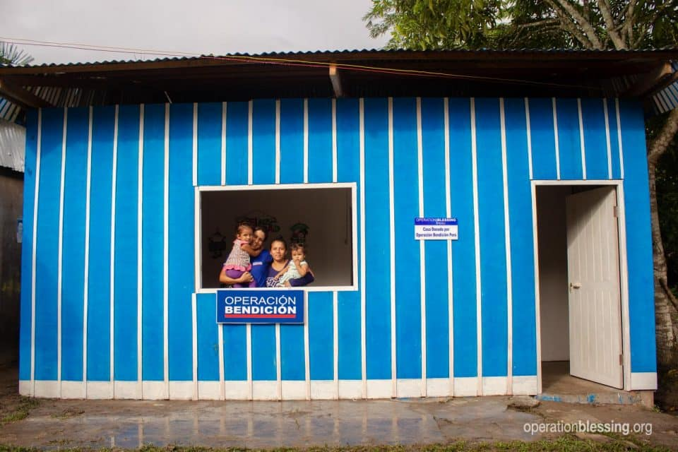 The family looks out the window of their new safe housing.