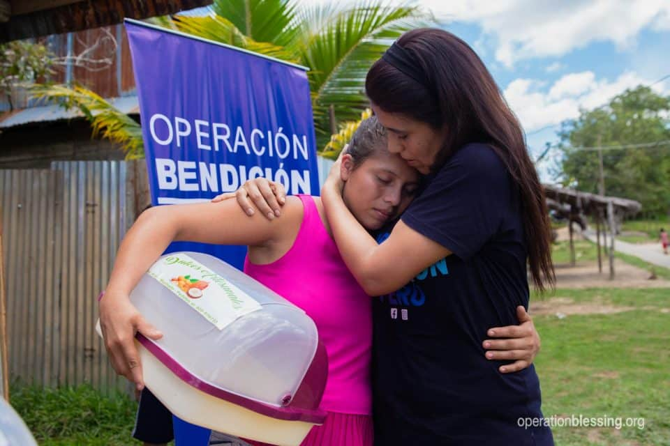 An Operation Blessing worker hugs and encourages Alany.