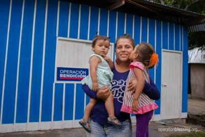 Alany and her daughters standing in front of their new safe housing from Operation Blessing.