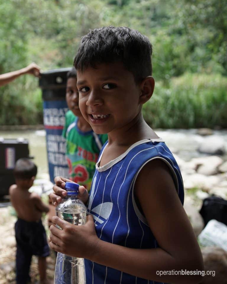 Refugee Emmanuel holds a bottle of clean water