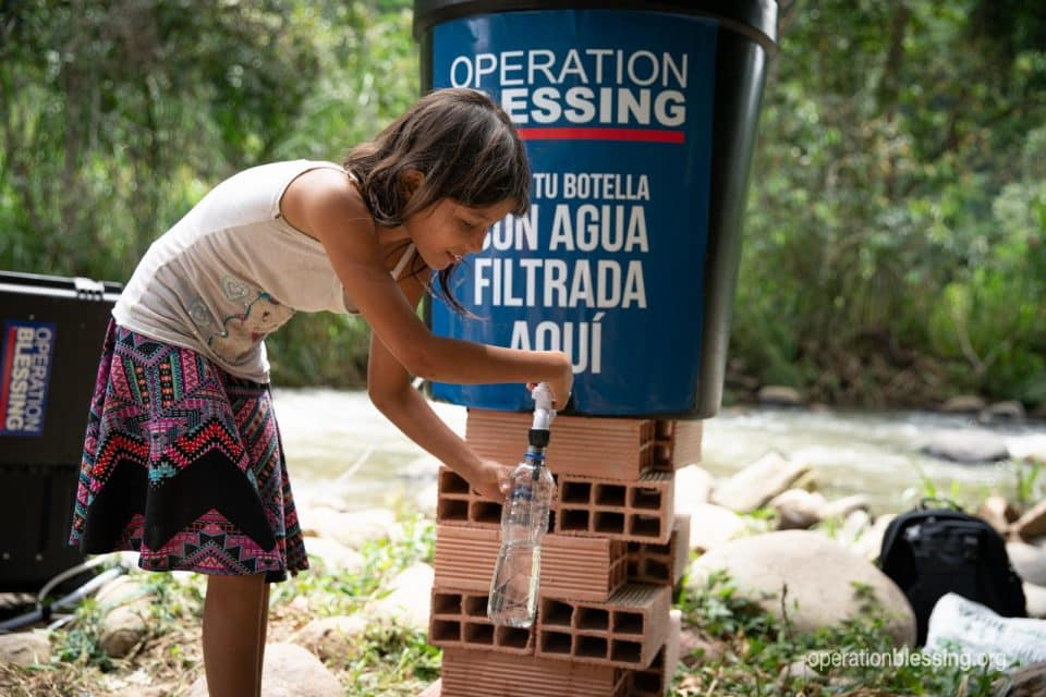 A young Venezuelan girl gets clean water at an Operation Blessing water station.