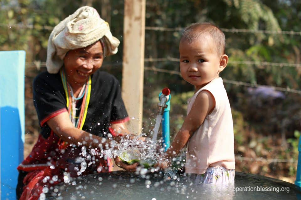 A woman and baby play in fresh, clean water in Cambodia.