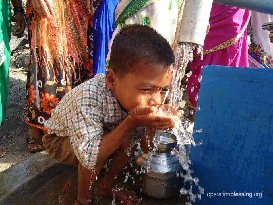 A boy drinks from a new water well in India.