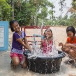 Young girls splashing in the water from new water wells provided by Operation Blessing supporters.