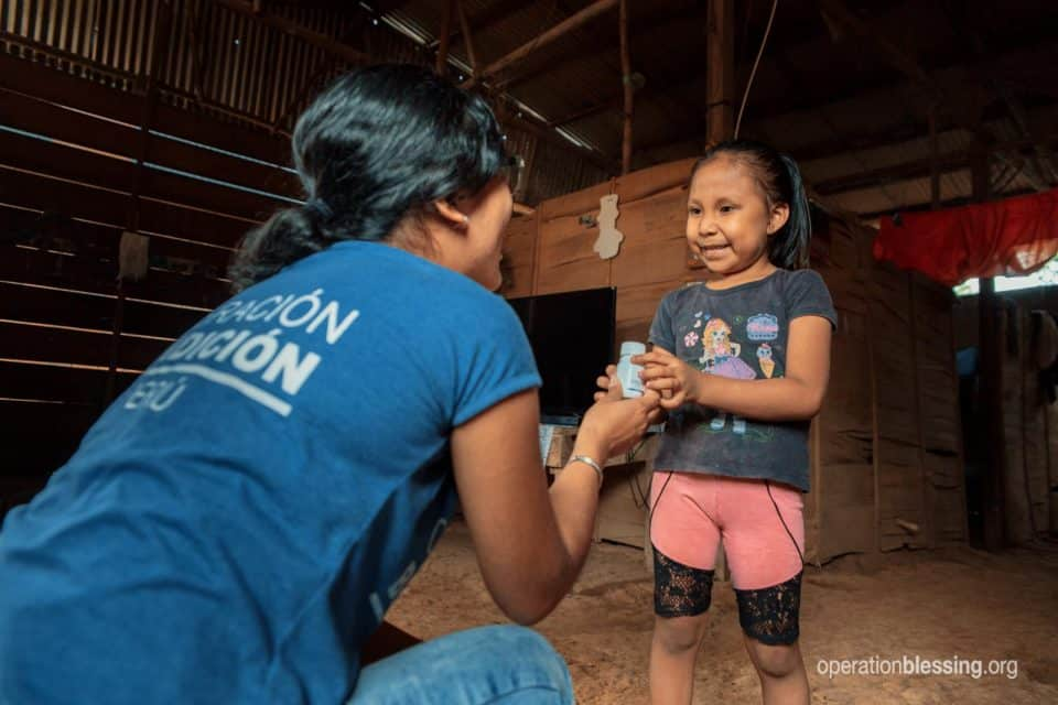 And Operation Blessing worker hands Candy free medicine to restore her health.