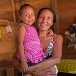 Candy with her mother, both smiling now that she received medical care.