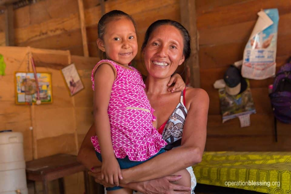 Candy with her mother, both smiling now that she received healing through free medical care.