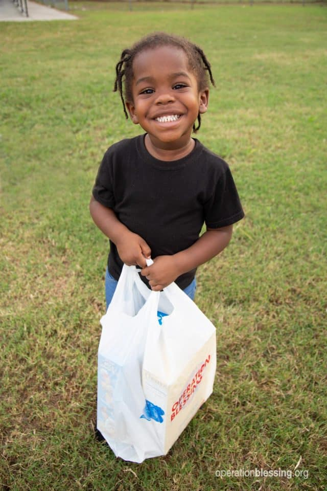 Eula's smiling granddaughter holds a bag of groceries.