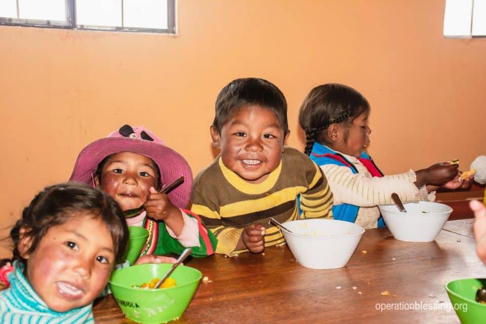 Children eat nutritious food through a feeding program in Peru.