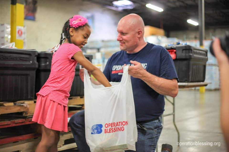 A young girl helps bag food for the summer feeding program.