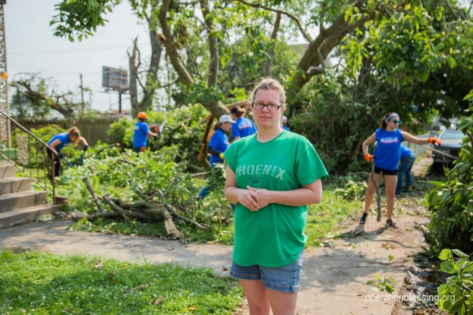 Nicole stands in her storm damaged yard as Operation Blessing volunteers provide tornado relief.
