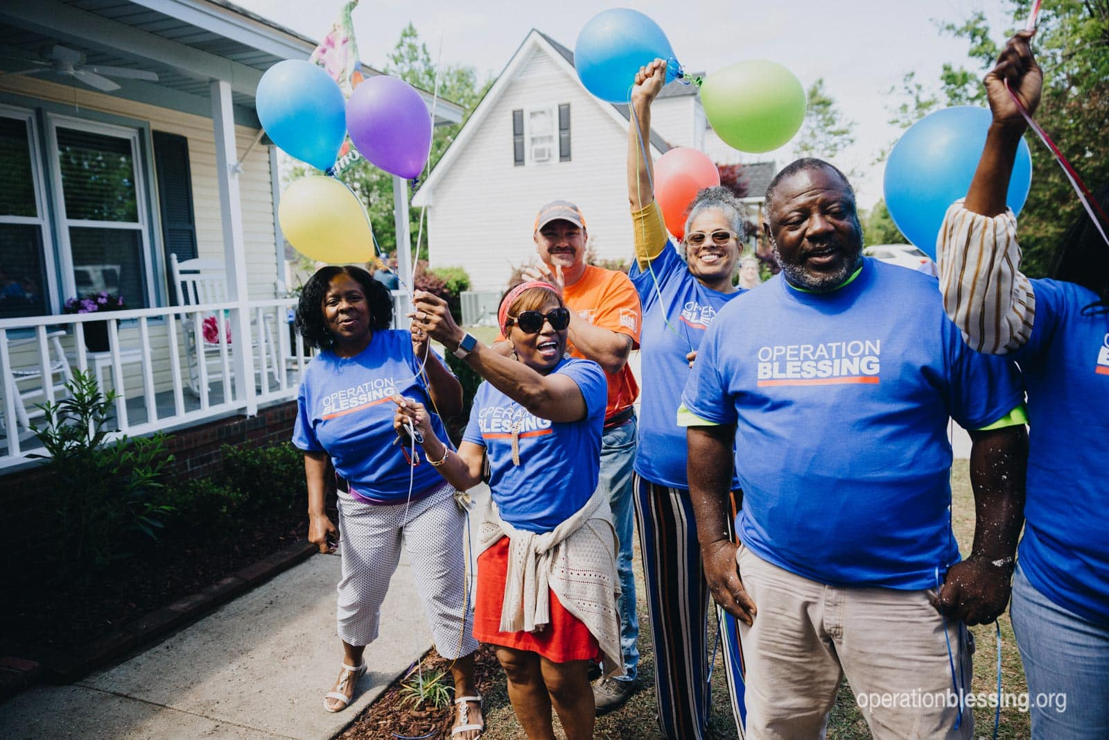 Operation Blessing volunteers greet the family and celebrate their triumph from tragedy.
