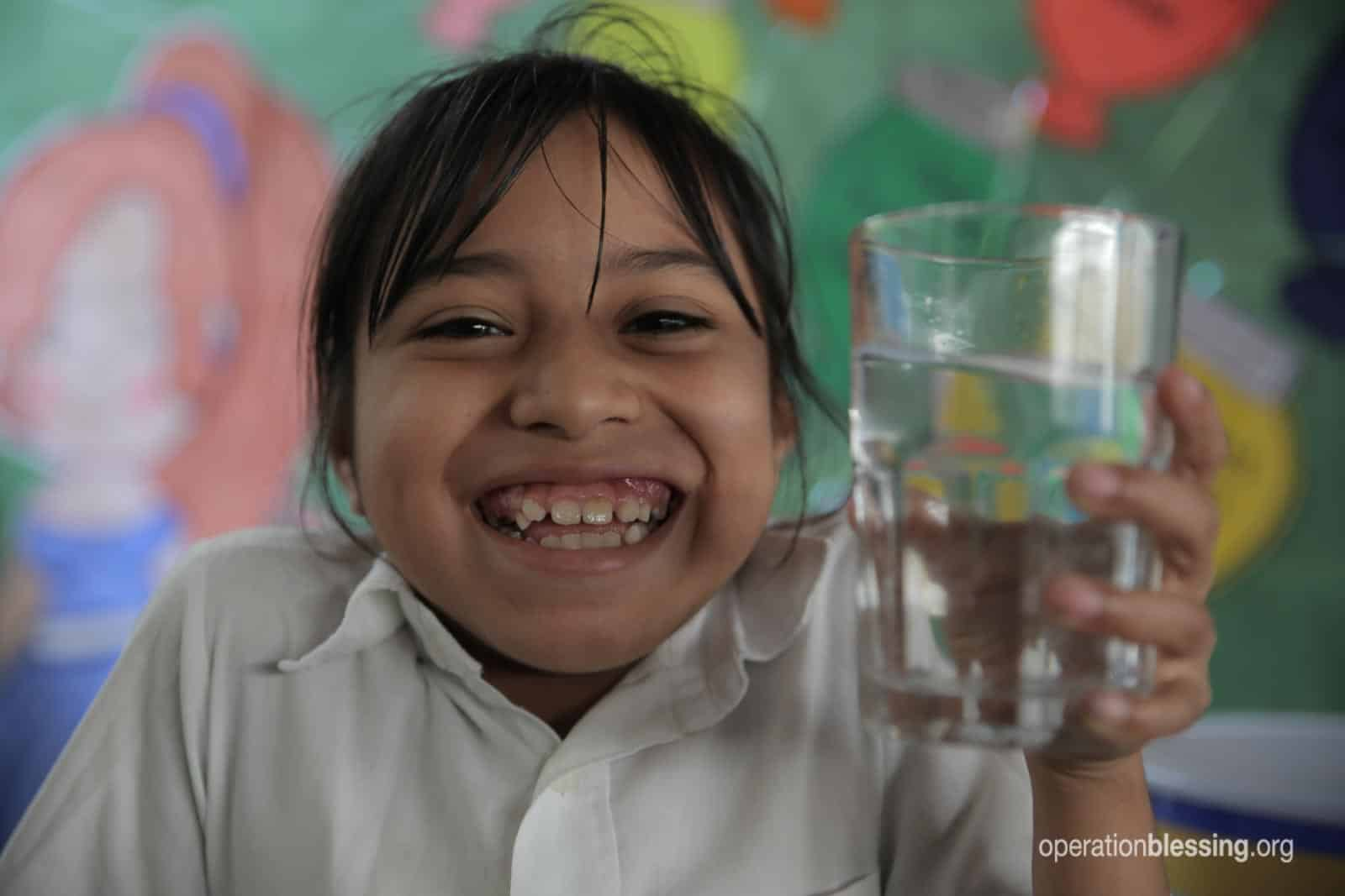 A female student smiles and holds a glass, no longer suffering without clean water.