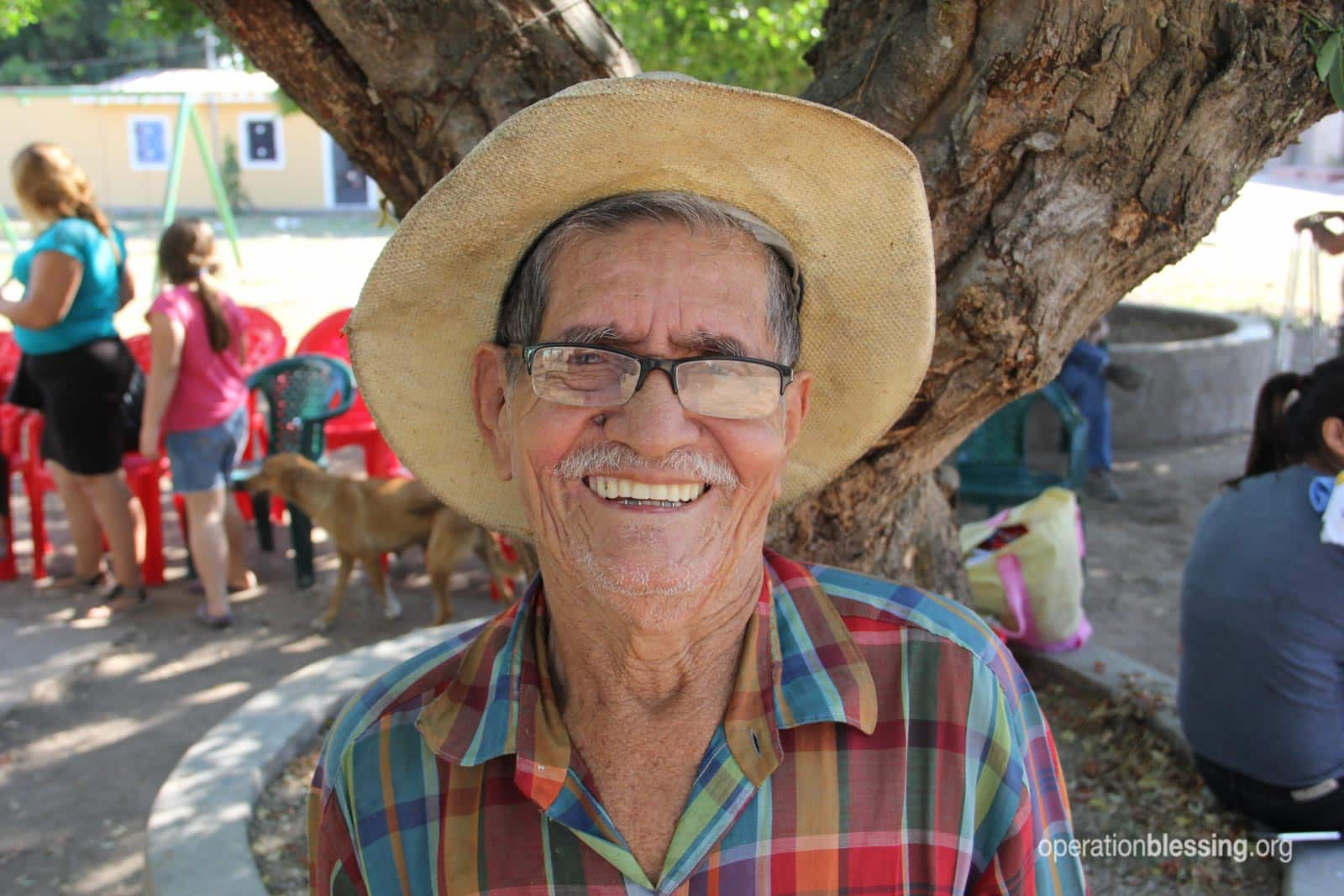 Francisco from El Salvador smiles after receiving the medicine he needs for high blood pressure.