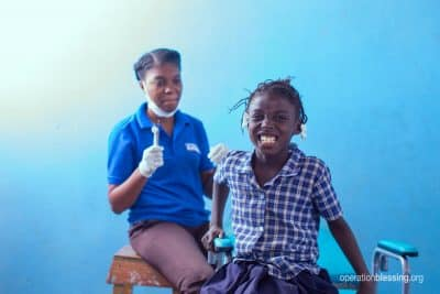 A Haitian girl smiles after free dental treatment from Operation Blessing friends.