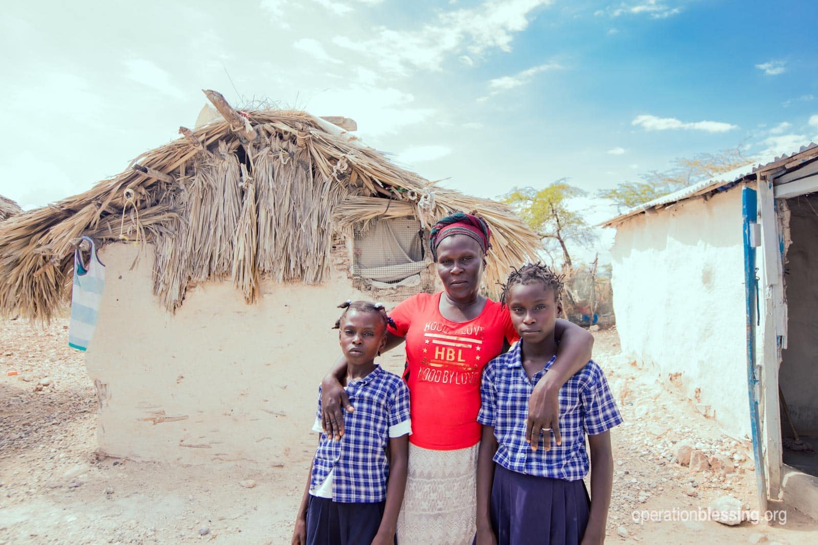 A Haitian family stands in front of their hut-like home.