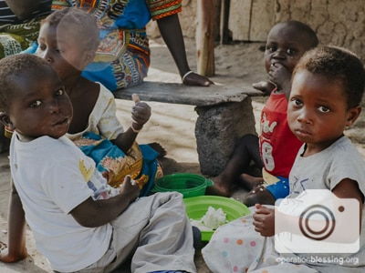Children in Mozambique eating food from Operation Blessing friends.