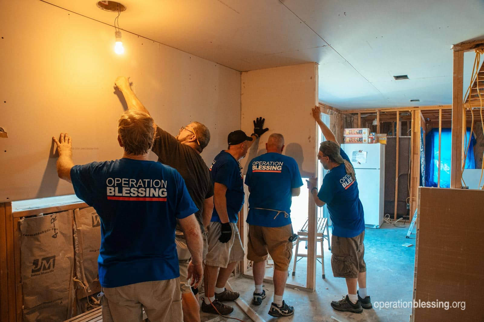 The whole Operation Blessing volunteer crew installing drywall.