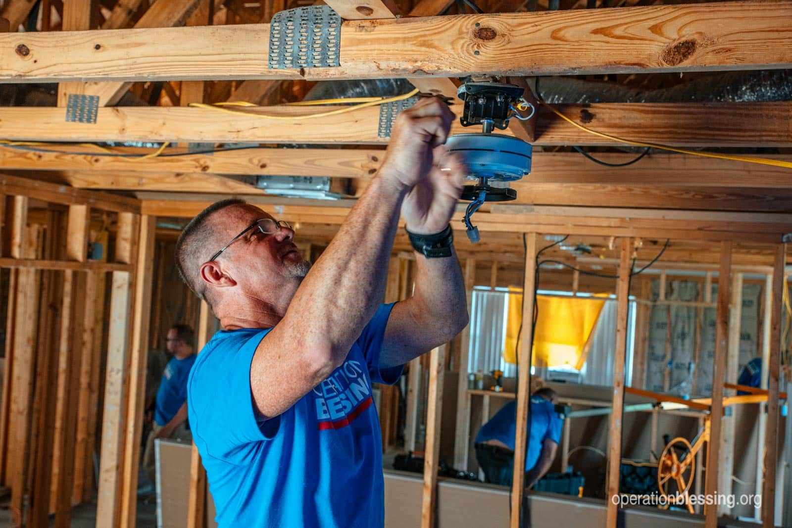 An OB volunteer repairing the Peterson's home.