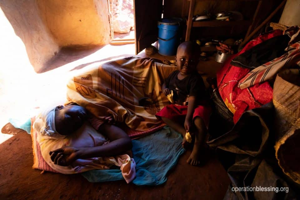 Idah lying sick in bed in Zimbabwe