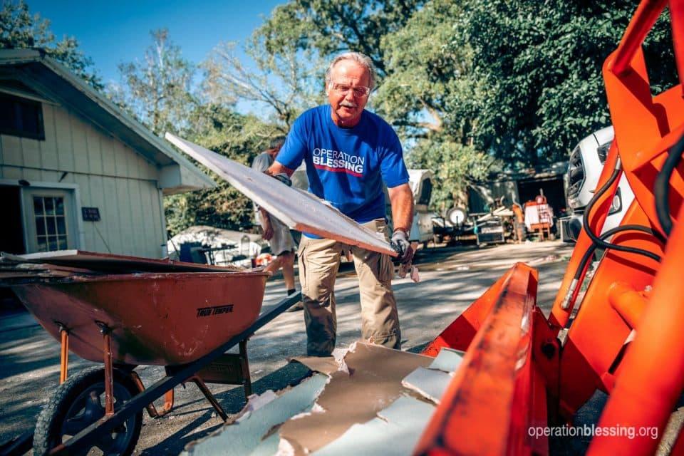 Disaster relief worker carrying debris in Beaumont, Texas.