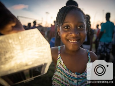 A young Hurricane Dorian victim receives a solar light in the aftermath.