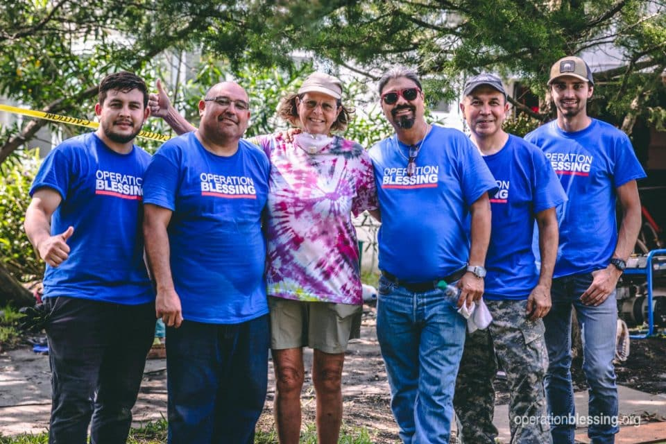 Grace surrounded by the support of Operation Blessing volunteer helpers.