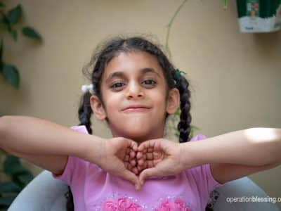 Persecuted Christian, Maryam, holds her hands in a heart.