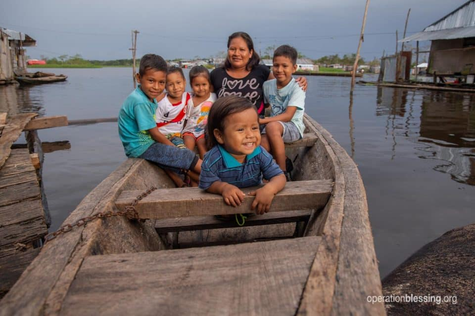 Celina and her family in a boat on the Amazon river of Peru.
