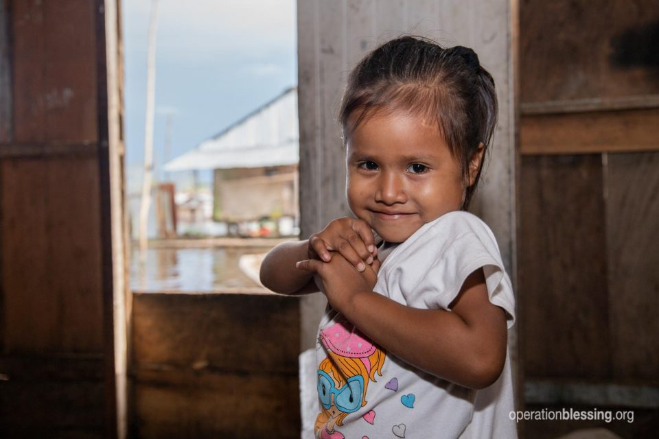 One of Celina's daughters stands by the window overlooking the flooded Amazon.