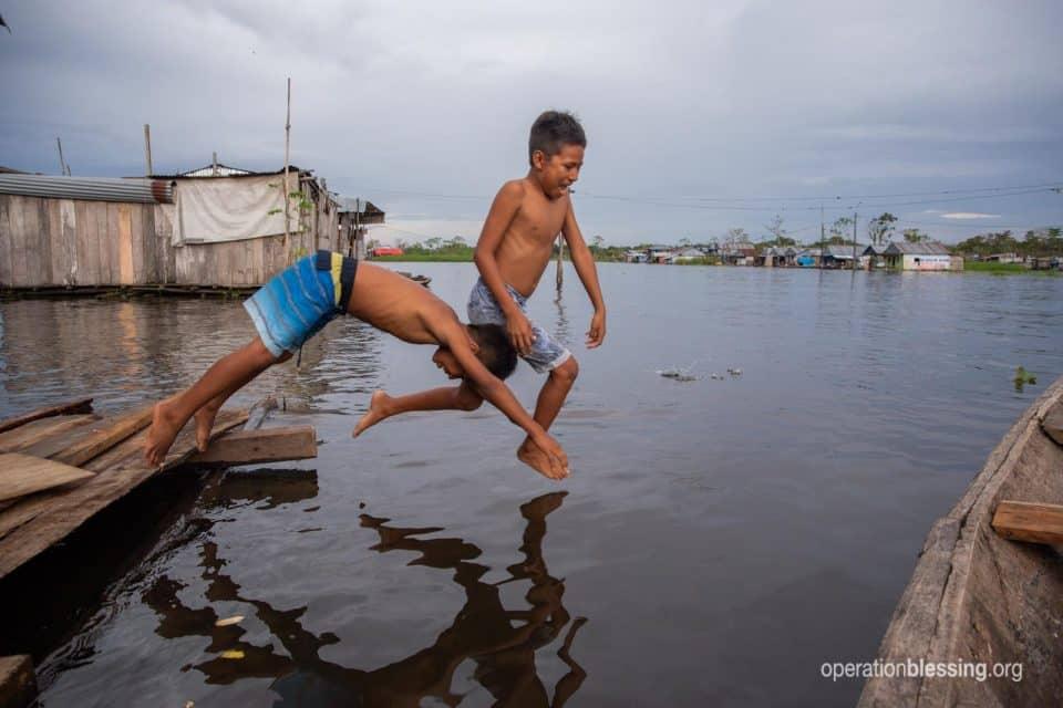 Celina's boys swim in contaminated flood waters.