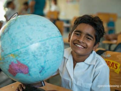 Young school boy with a new globe.