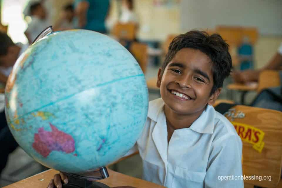 Young school boy with a new globe at his safe school.