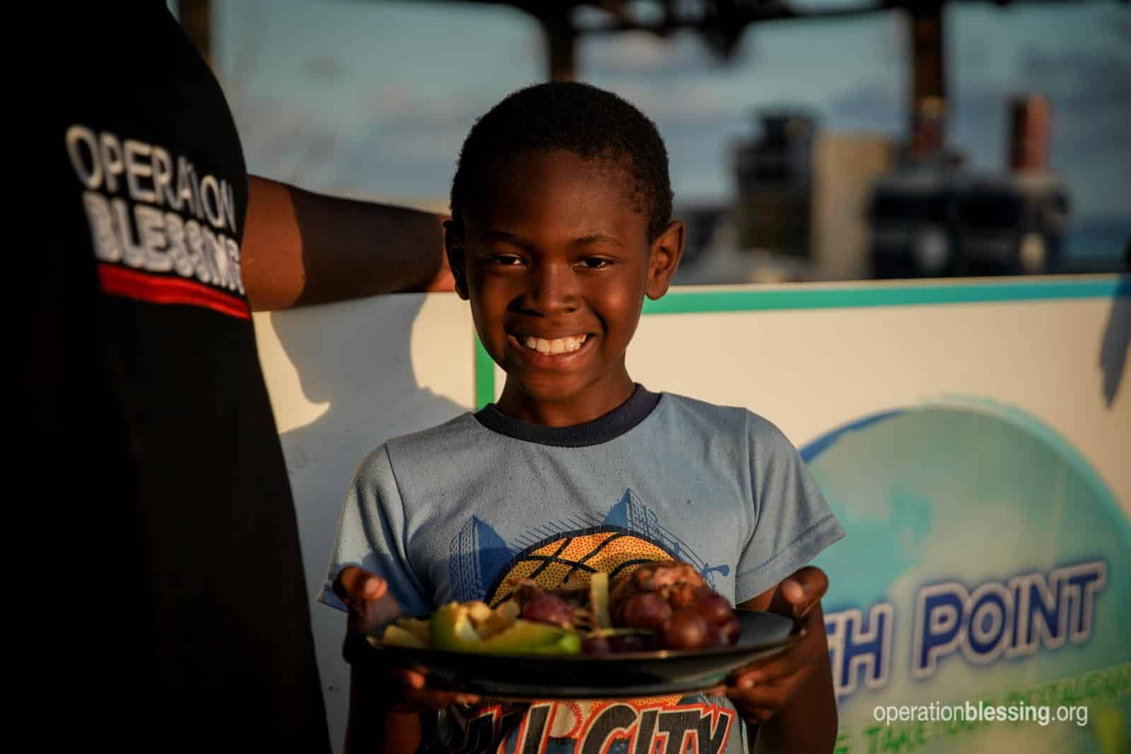 Happy boy in the Bahamas holding food after Hurricane Dorian.