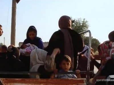 Kurdish refugees entering Iraq, like the children on this truck, need relief and aid.