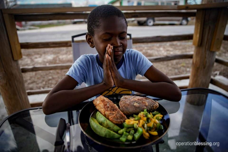 Beverly's grandson prays over the first meal in the newly repaired restaurant.