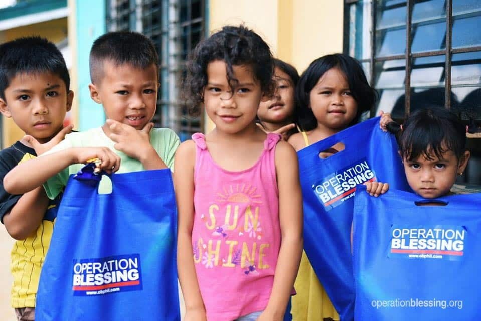 Happy children holding disaster relief kits in the Philippines.