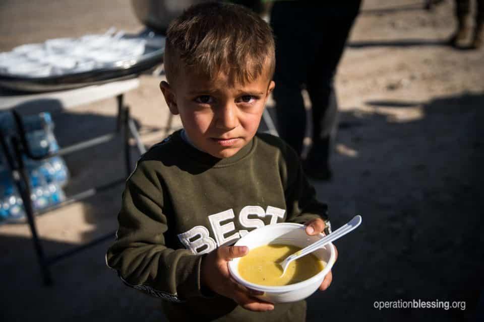 Sad boy, refugee getting food in Syria.