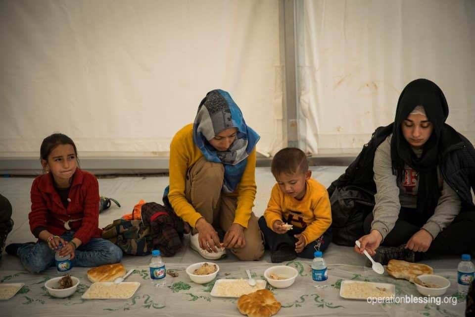 Family of Syrian refugees eating a hot meal thanks to OB friends.