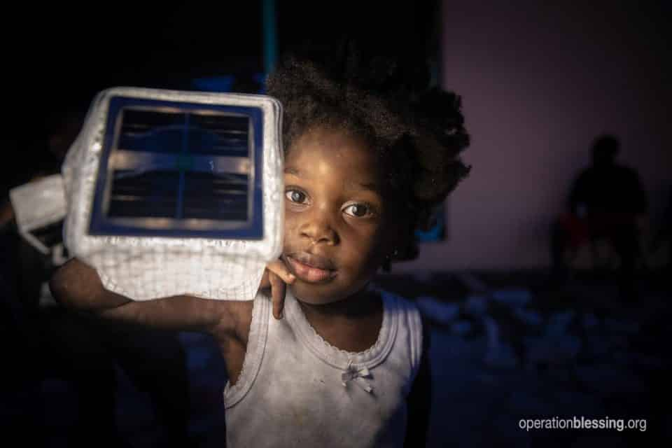 Young victim of Hurricane Dorian holds solar light