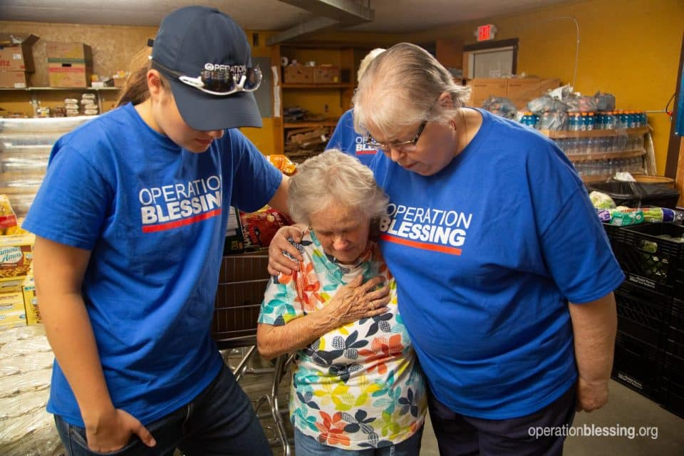 Betty gets prayer from hunger relief volunteers.