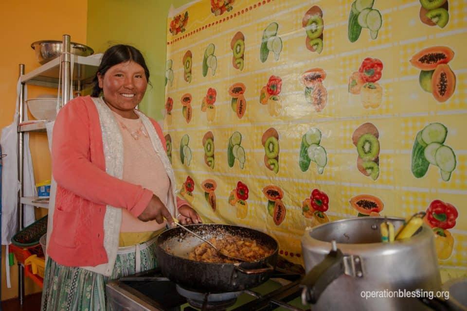 Julieta cooking healthy meals for school kids in Peru.