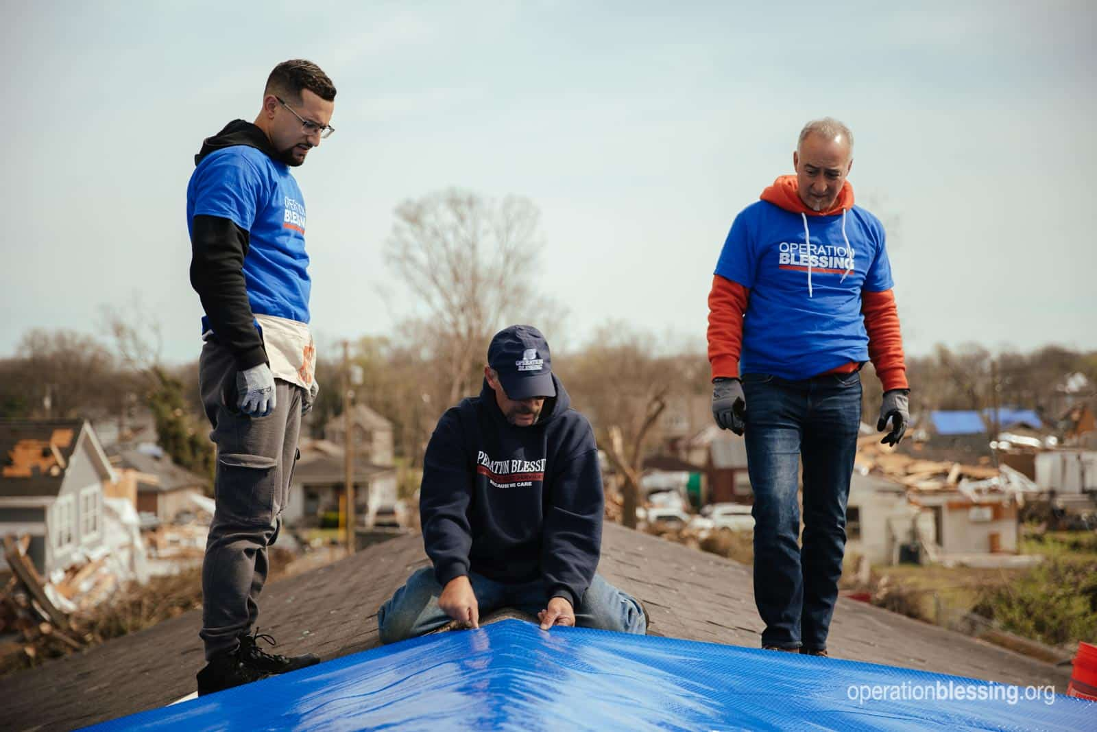 Operation Blessing staff and volunteers tarping Patrice's damaged roof.