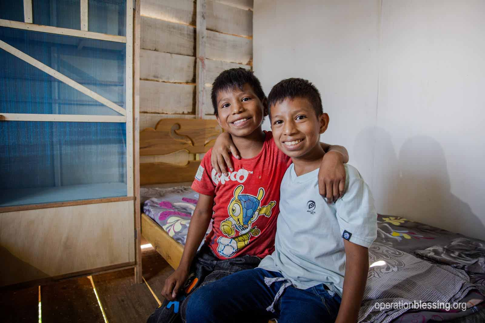 Happy boys after their family received a new home and business in Peru.