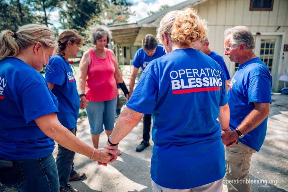 Volunteers pray with Brenda after Imelda in Texas.