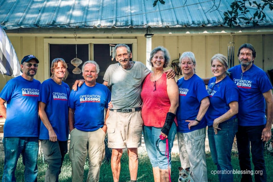 A team of disaster relief workers surround Brenda and Gerald as the blessings come back to them.